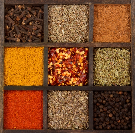 assorted herbs and spices in a decorative box, cloves, nutmeg, curry, chili powder, crushed chillies, dill seed, thyme, peppercorn, anise Foto de archivo