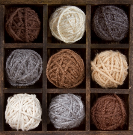 handicrafts: Assorted balls of natural colored yarn in a printers box Stock Photo