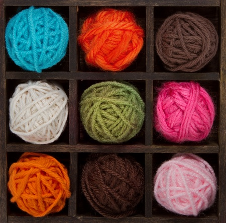 Nine colorful balls of yarn in a printers box, in autumn colors
