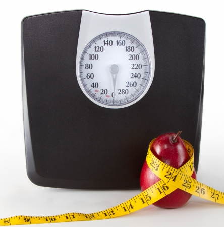 Close up of a scale and an apple or pear with a measuring tape on a white background, room for copy-space on scale. Foto de archivo