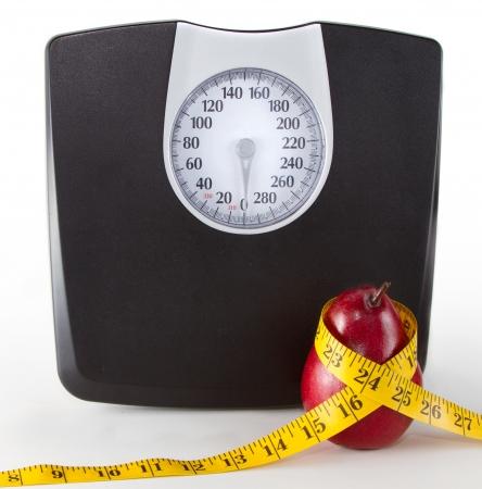 balanza en equilibrio: Primer plano de una escala y una manzana o una pera con una cinta m�trica sobre un fondo blanco, espacio para la copia de espacio en la escala.