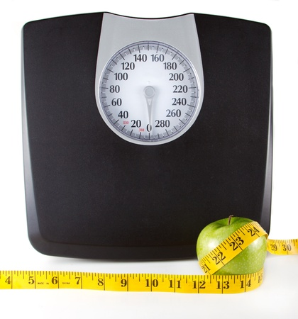 weighing: An apple with a measuring tape around it with a scale in the background, white background. Room for copy-space on the scale.