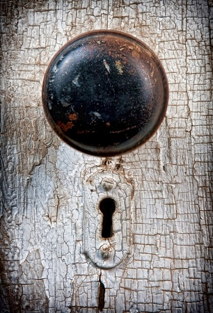 Rustic vintage doorknob on antique door, background photo