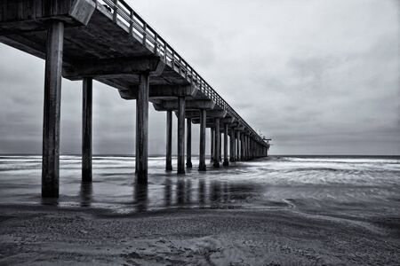 La Jolla beach, California,  long exposure under the pylons, black and white image. photo