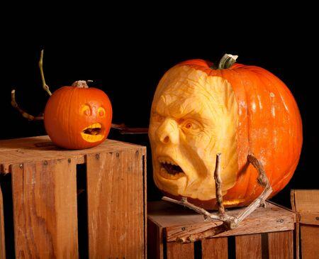 carving pumpkin: Halloween Jack-o-linterna de calabaza talla muy detallada, sentados sobre cajas de madera con un fondo negro