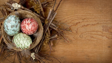 Decorative easter eggs made of paper in nest on a wooden background, room for copyspace. photo