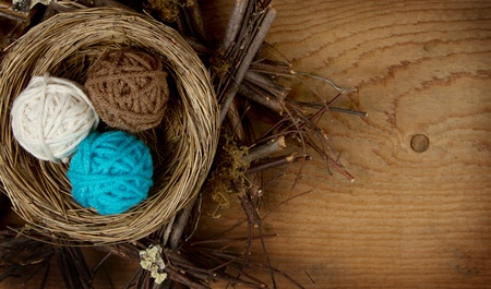 craft materials: Balls of yarn in a nest easter decoration, on a wooden background, room for copyspace.