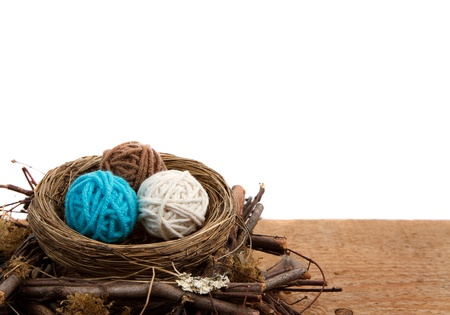 Balls of yarn in a nest easter decoration, on a white isolated background, room for copyspace. photo