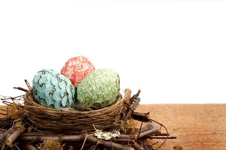 paper covered easter eggs in a nest on a white background room for copy space photo