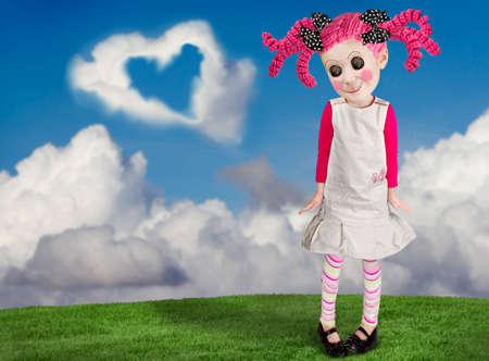 A little girl that looks like a doll, with a blue sky and clouds background room for copy space.