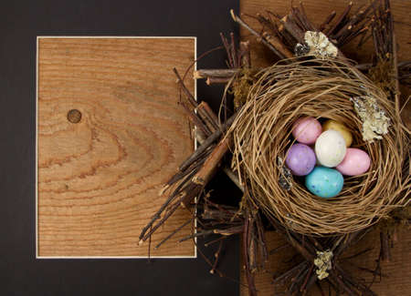 easter nest: easter candy in a nest with a frame on wooden background