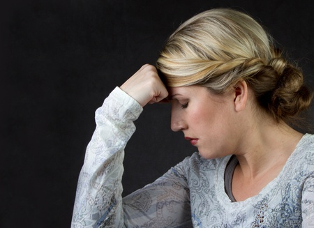 A woman deep in thought or with a headache, against a dark background room for copyspace Reklamní fotografie