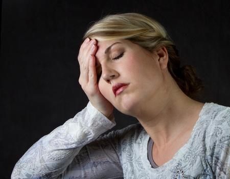 A woman that is upset, depressed or has a headache Foto de archivo