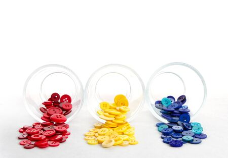 sewing buttons: Sewing buttons spilling from jars in primary colors, red yellow and blue Stock Photo