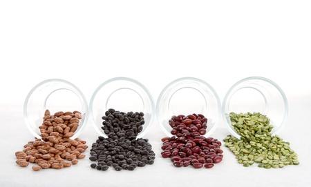 bönor: Bönor och ärter spiller ut ur glasburkar på en vit bakgrund