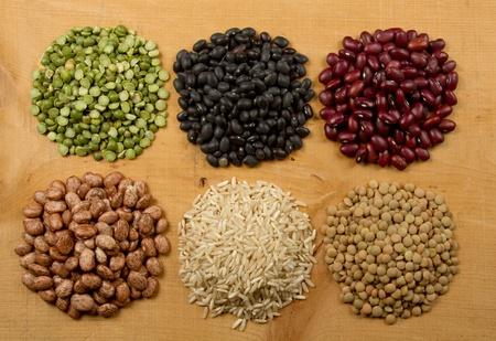 leguminosas: Montones de guisantes frijoles arroz y lentejas en una tabla de madera