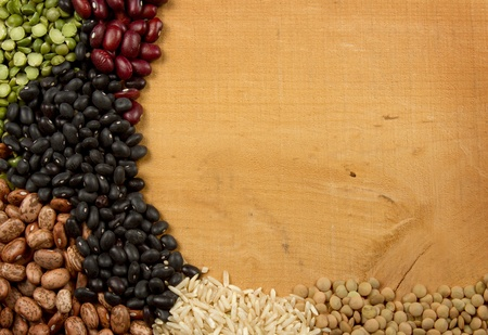 Piles of beans rice peas and lentils on a wooden plank room for copy space photo