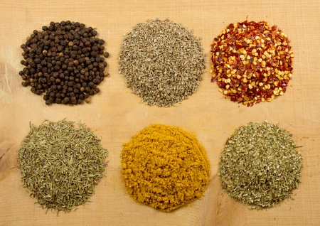 Assorted herbs and spices on a wooden plank Stock Photo - 12761736