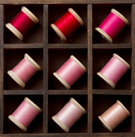 old spools: Vingtage pink and red spools of thread in a wooden printers box Stock Photo