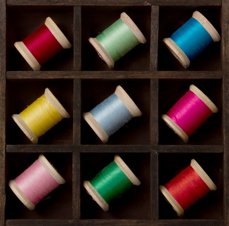 Vintage spools of thread in many colors, arranged in a printers box Stock Photo - 12903412