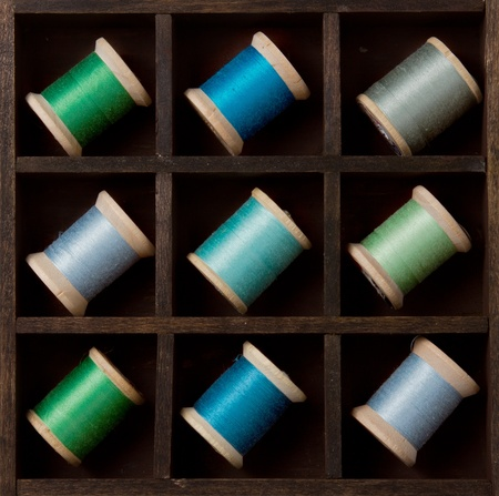Vintage spools of thread in blues and greens in a printers box Stock Photo - 12761358
