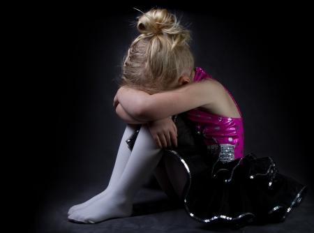 A sad dancer in a spotlight on a black background