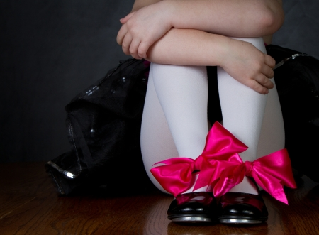 Tap shoes on a little girls feet, dark background room for copy space Stock Photo