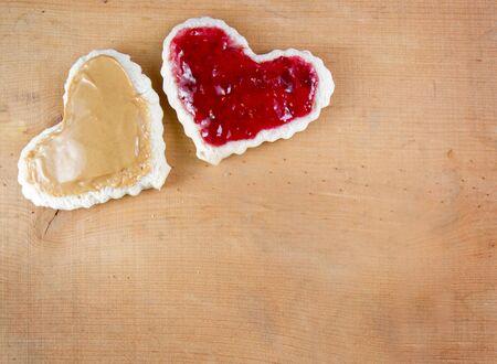 cacahuate: Mantequilla de maní y jalea de sandwitch corte en forma de corazón sobre una tabla de madera Foto de archivo