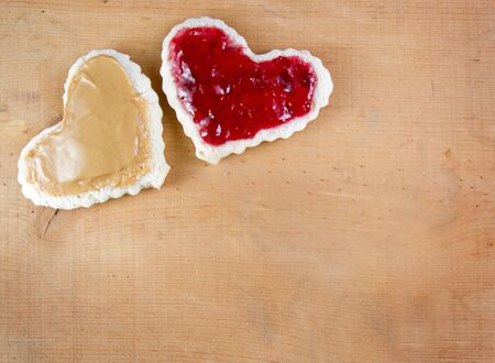 peanut butter and jelly sandwich: Peanut butter and jelly sandwitch cut in a heart shape on a wooden board Stock Photo