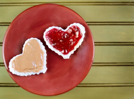 A heart shaped peanut butter and jelly sandwitch on a plate photo