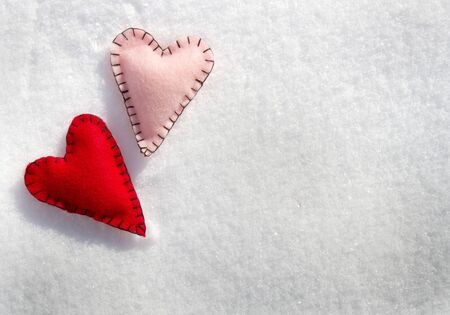 Two stitched hearts on a snowy background photo
