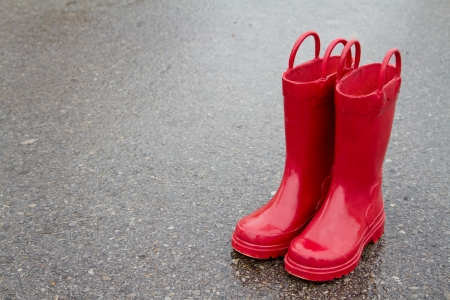 work boots: Red rain boots on wet pavement, room for copy space