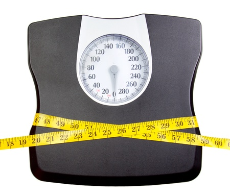 A bathroom scale with a measuring tape, weight loss concept Foto de archivo