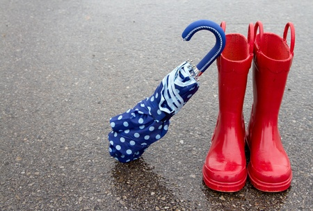 lluvia paraguas: Botas de lluvia y el paraguas rojo de lunares en el pavimento mojado