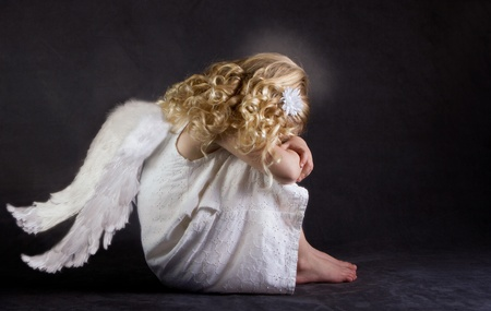 A fallen angel or child angel who is sad photo
