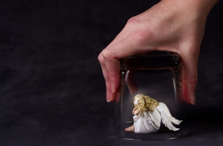 hopelessness: An angel trapped under a glass, a child angel or fallen angel Stock Photo