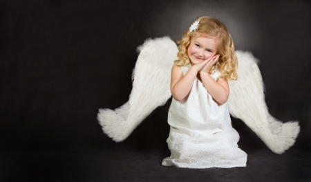 gothic angel: A smiling angel sitting with her hands near her face