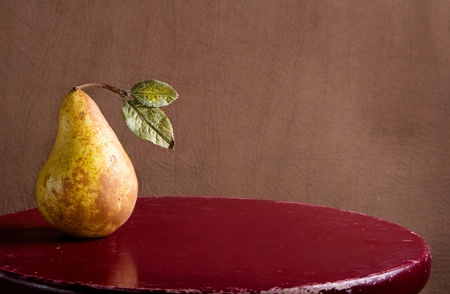stools: a pear on a rustic stool still life Stock Photo