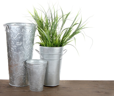 Metal gardening containers with grass on a white background photo