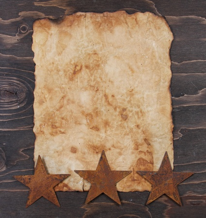 Vintage paper on a wooden background with rusty stars vertical photo