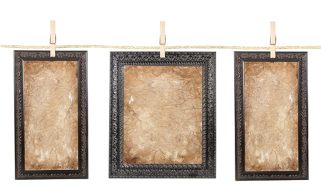 line: Three picture frames with aged paper isolated on a clothes line