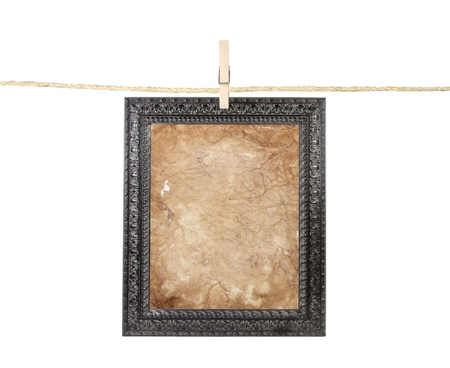 Picture frame with aged paper isolated on a clothes line Stock Photo