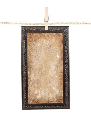 Long picture frame with aged paper isolated on a clothes line  photo