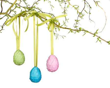 Three Easter eggs hanging from a branch isolated on white photo