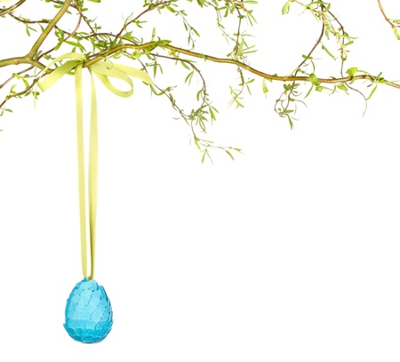 Single Easter egg hanging from branch, isolated on white photo