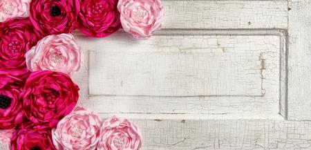 Roze vintage bloemen op oude gebarsten deurpaneel Stockfoto
