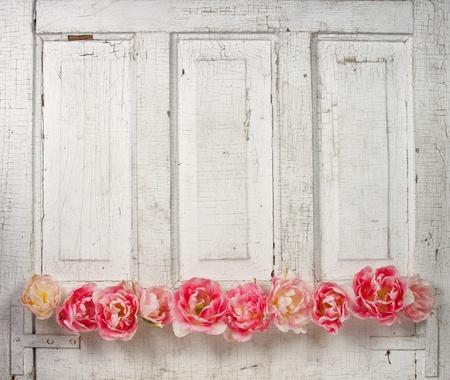 Bloemen op een lambrisering vintage deur, (roze tulpen en rozen als bloemen)