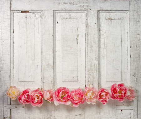 Flowers on a paneled vintage door, (pink tulips or roses like flowers) Stock Photo
