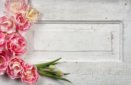 Flowers on a paneled vintage door, (pink tulips or rose like flowers)