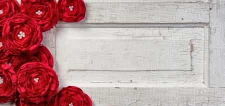ビンテージのドアに赤いぼろぼろシックな花 写真素材
